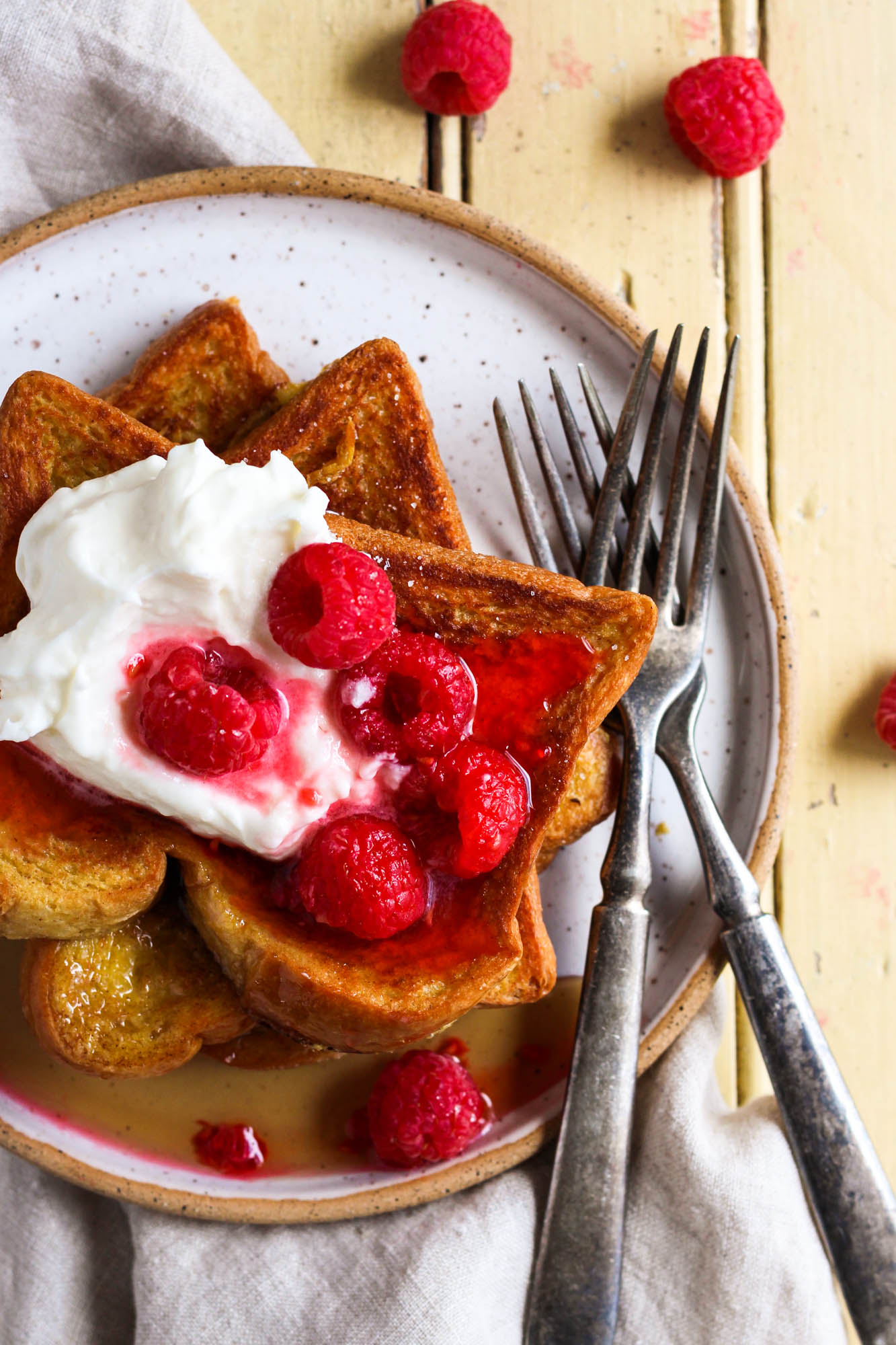 Top view of cinnamon french toast with rapsberries and lemon whipped cream