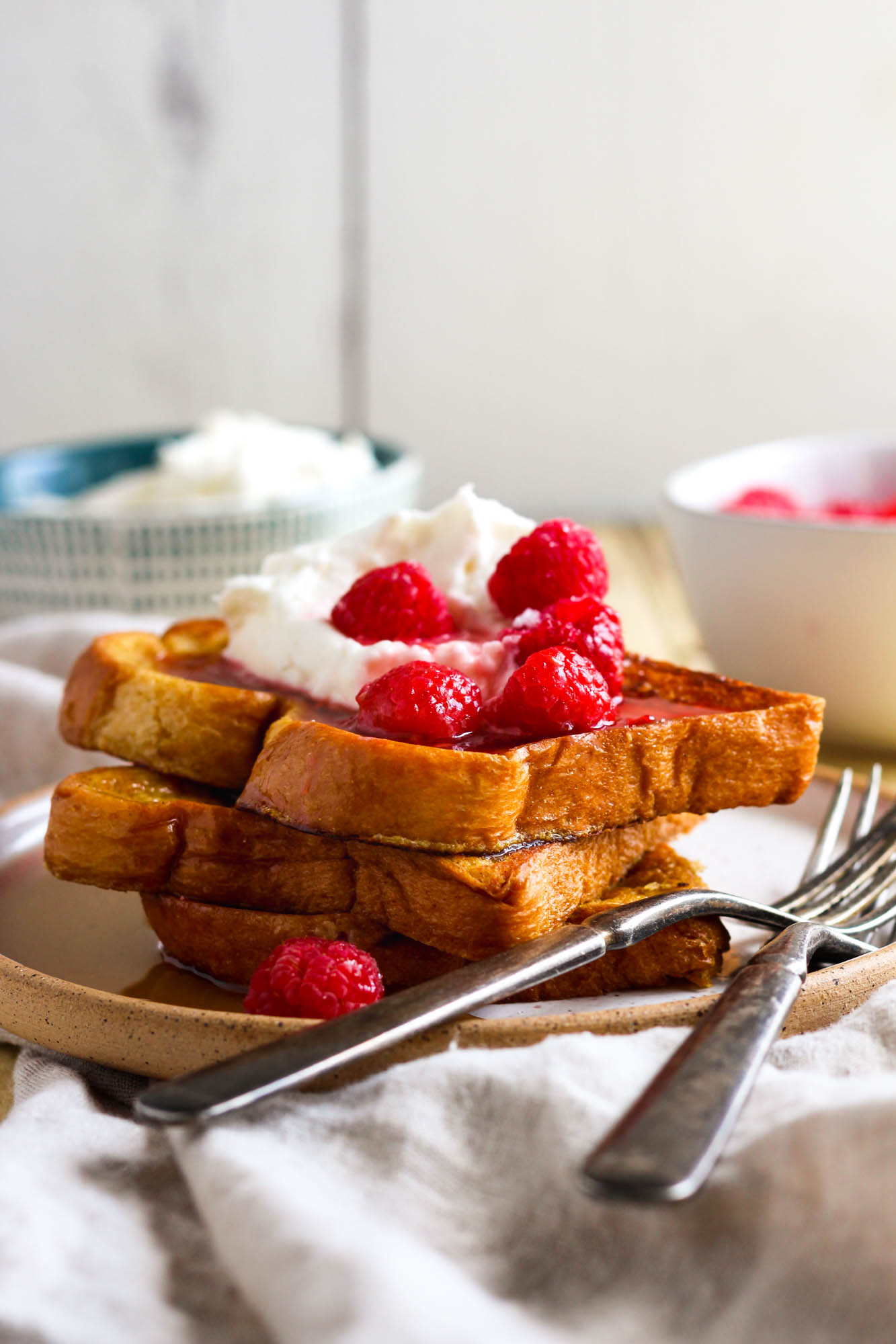 Cinnamon French toast topped with raspberries and lemon whipped cream