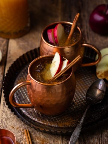 spiced apple cider moscow mule in copper mug with apple slices and cinnamon sticks
