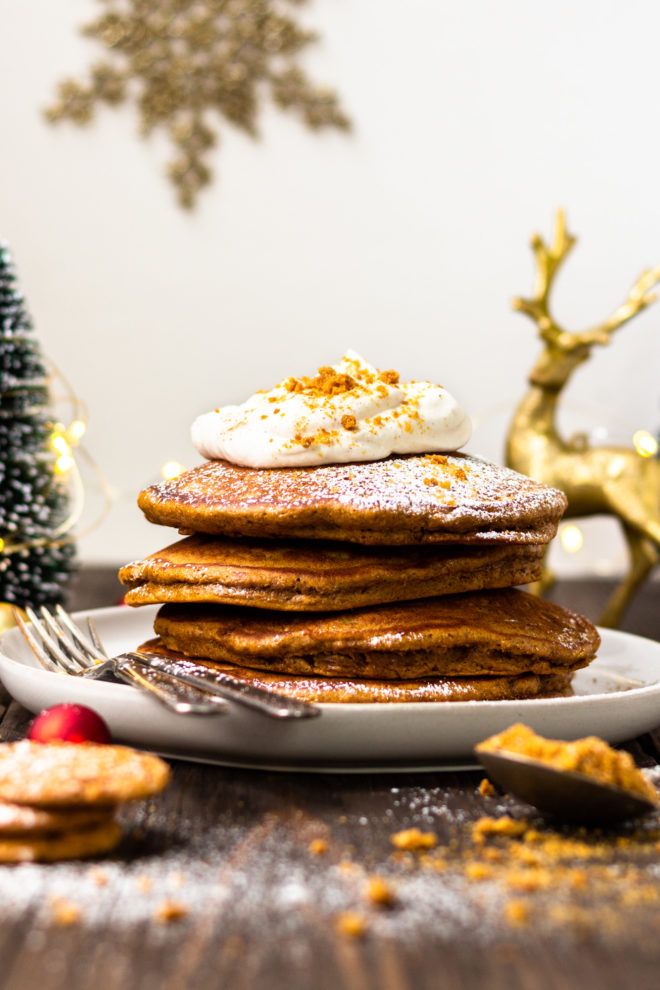 stack of gingerbread pancakes on a plate with eggnog whipped cream