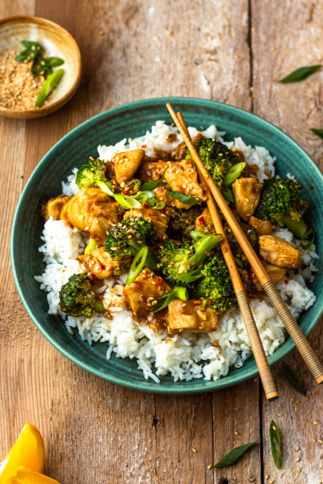 orange chicken and broccoli over rice in a bowl with chopsticks