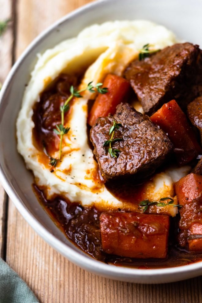 The most delicious and cozy bowl of comfort food! Venison {or beef} roast and carrots slowly cooked with brown ale beer, beef broth, and fresh herbs until flavorful, tender perfection! Serve over a bed of creamy mashed potatoes and don't forget to drizzle the gravy over the top! Instructions included for oven, crock pot and instant pot!