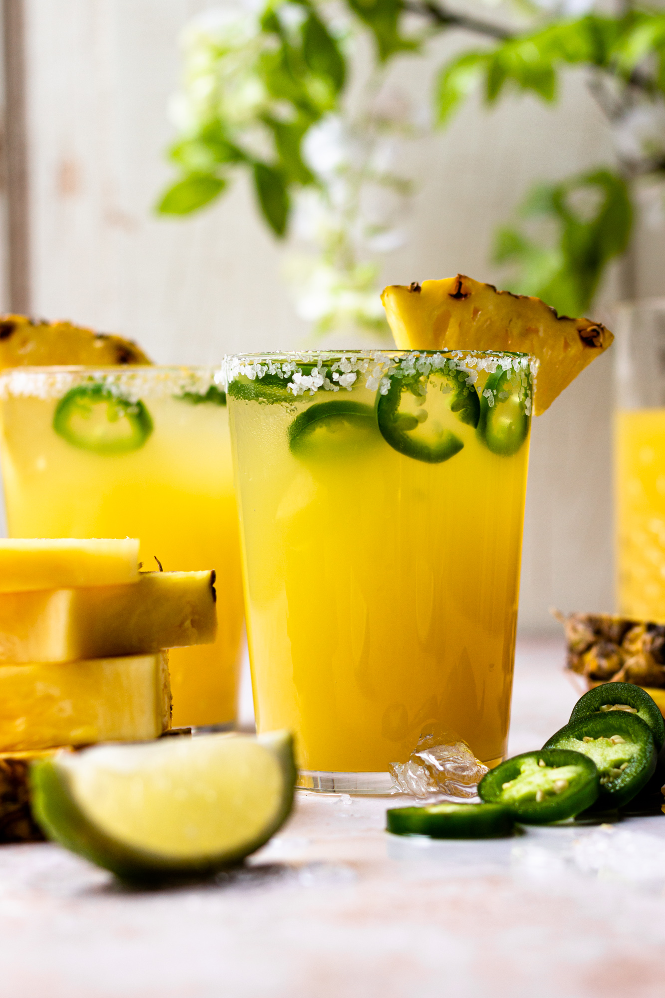 Refreshing and delicious pineapple margarita with a little kick of heat! This fun cocktail is perfect for sipping on a warm, sunny day, and is only lightly sweetened with pineapple juice. Add your desired level of spice by adding more or less jalapeño slices, or omit them if spicy isn't your thing. The cocktail will still taste great!