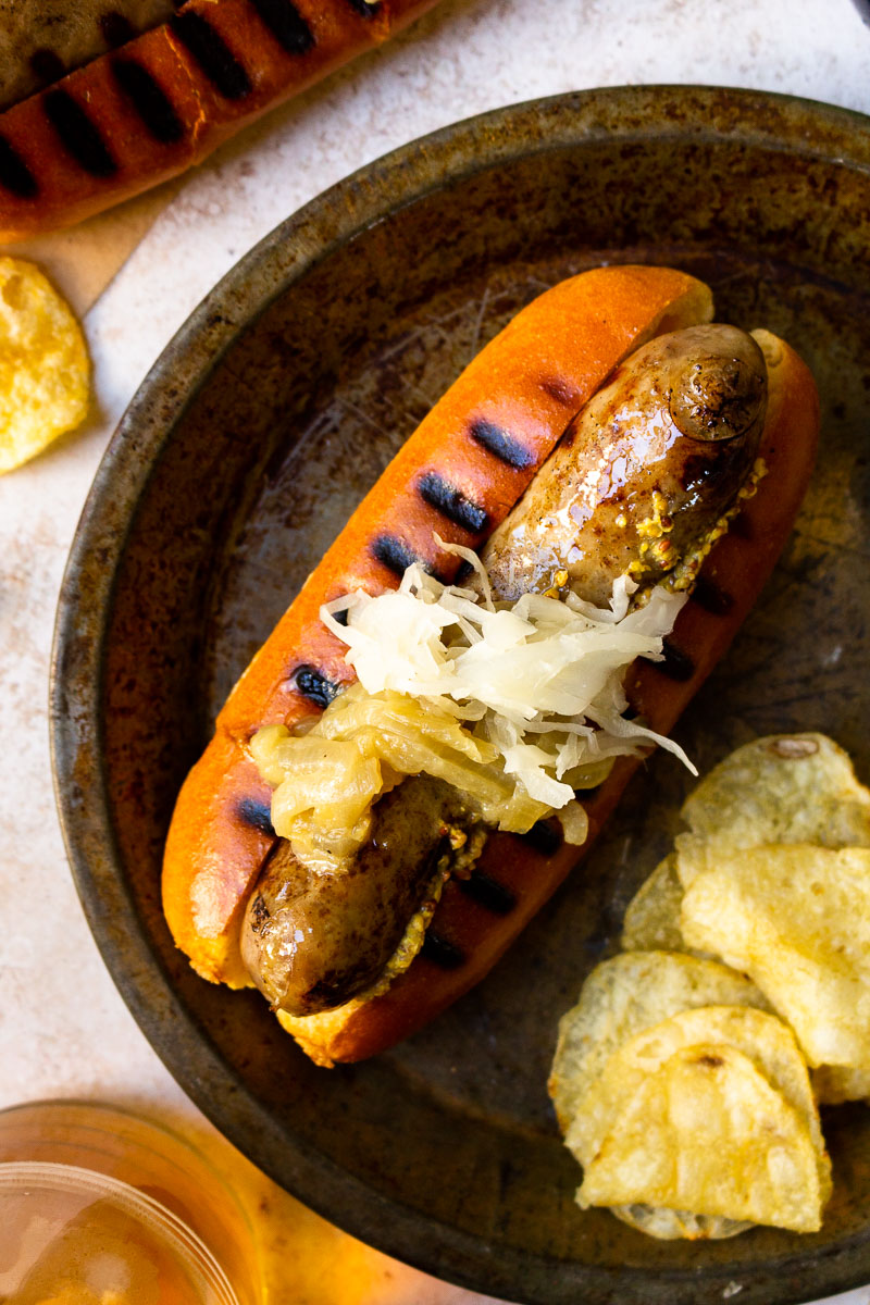 beer brat topped with caramelized onions and sauerkraut