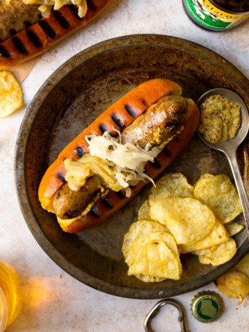 beer brat served with chips and beer