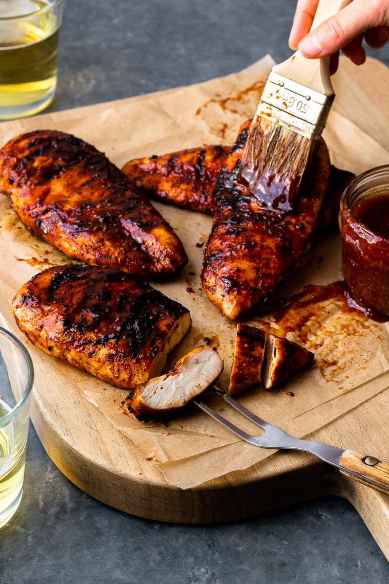 brushing bbq sauce on grilled chicken