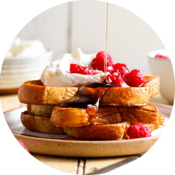French toast with whipped cream, raspberries and maple syrup
