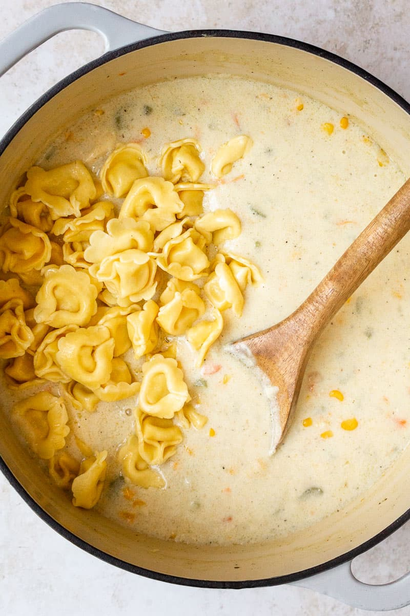 mixing cheese tortellini into soup